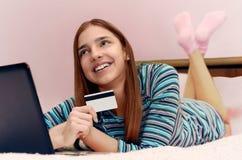 使用膝上型计算机,年轻美丽的微笑的女孩做网上购物 免版税库存图片