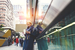 使用自由wifi连接,年轻美丽的金发碧眼的女人由工作常设外部旅行 免版税图库摄影