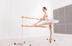 使用芭蕾酒吧的逗人喜爱的年轻芭蕾舞女演员 免版税库存图片
