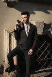 使用葡萄酒影片照相机的英俊的年轻商人 库存图片