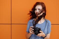 使用葡萄酒影片35mm照相机的一个美丽的女孩的画象 免版税库存图片