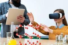 使用虚拟现实玻璃和3D介绍的年轻老师教化学班的学生 教育, VR,个别辅导 免版税图库摄影