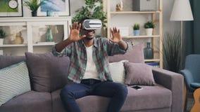 使用虚拟现实玻璃微笑和笑在长沙发和移动手享用的非裔美国人的人开会 股票视频
