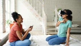 使用虚拟现实玻璃的混杂赛跑的妇女,当她的拿着数字式片剂计算机时的朋友 女朋友戏剧录影 库存图片