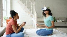 使用虚拟现实玻璃的混杂赛跑的妇女,当她的拿着数字式片剂计算机时的朋友 女朋友戏剧录影 免版税库存图片