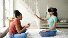 使用虚拟现实玻璃的混杂赛跑的妇女,当她的拿着数字式片剂计算机时的朋友 女朋友戏剧录影 免版税库存照片