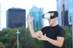 使用虚拟现实玻璃的男性在城市 免版税库存照片