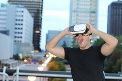 使用虚拟现实玻璃的男性在城市 免版税库存图片
