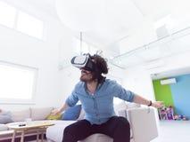 使用虚拟现实的VR耳机玻璃人 库存照片