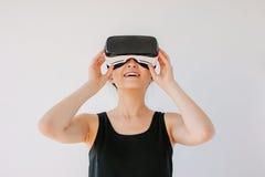 使用虚拟现实耳机和微笑的少妇 免版税库存图片