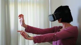 使用虚拟现实耳机的妇女在客厅4k 股票视频