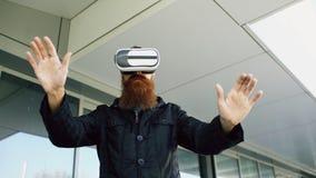 使用虚拟现实耳机的年轻有胡子的人为360个VR经验,当步行沿着向下城市街道户外时 图库摄影