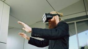 使用虚拟现实耳机的年轻有胡子的人为360个VR经验,当步行沿着向下城市街道户外时 免版税库存照片