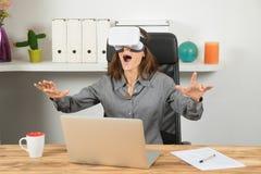 使用虚拟现实耳机的愉快的女实业家在工作场所 免版税库存照片