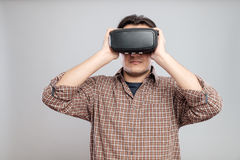 使用虚拟现实耳机的愉快的年轻人 免版税图库摄影