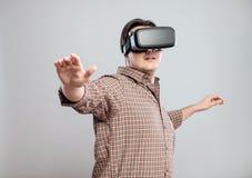 使用虚拟现实耳机的愉快的年轻人 免版税库存照片