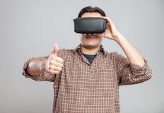 使用虚拟现实耳机的愉快的年轻人 免版税库存图片
