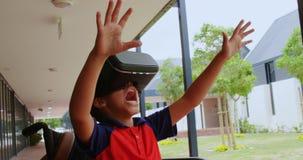 使用虚拟现实耳机的残疾非裔美国人的男小学生正面图在学校走廊4 股票视频