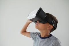 使用虚拟现实耳机的男小学生 免版税库存照片