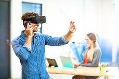 使用虚拟现实耳机的年轻人,当谈话在电话时 库存图片