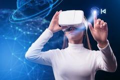 使用虚拟现实设备的严肃的少妇 库存照片