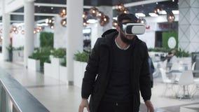 使用虚拟现实风镜的年轻人在购物中心,被弄脏的背景 影视素材