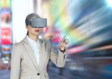 使用虚拟现实玻璃的女实业家反对城市在背景 库存图片