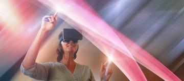 使用虚拟现实玻璃的微笑的成熟妇女的综合图象 免版税库存图片