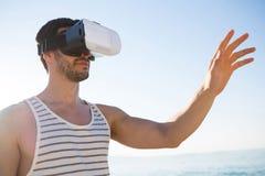 使用虚拟现实玻璃的年轻人在海滩 库存照片