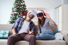 使用虚拟现实vr玻璃的愉快的家庭在圣诞节期间 库存图片