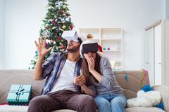 使用虚拟现实vr玻璃的愉快的家庭在圣诞节期间 免版税图库摄影