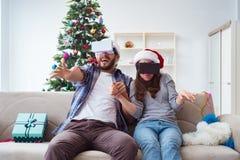 使用虚拟现实vr玻璃的愉快的家庭在圣诞节期间 免版税库存图片