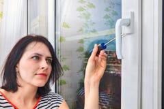使用螺丝刀,女孩解析PVC窗口的把柄 免版税库存图片