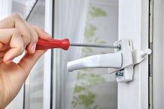 使用螺丝刀,安装塑料窗口的防幅器,关闭 免版税库存照片