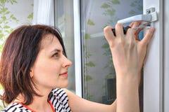使用螺丝刀,少妇松开窗口把柄 免版税图库摄影