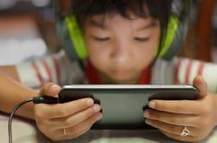 使用观看新的技术的新一代孩子演奏或动画片 图库摄影