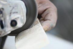使用角度研磨机切口瓦片的建筑工人 免版税库存图片