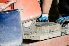 使用角度研磨机的建筑承包商切开一块铺路石 库存照片