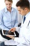 使用触感衰减器或片剂个人计算机的男性医生,当咨询女性患者在医院办公室时 医学和医疗保健 库存图片