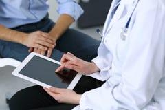使用触感衰减器或片剂计算机的女性医生,当咨询人患者在医院时 医学和医疗保健 免版税库存照片