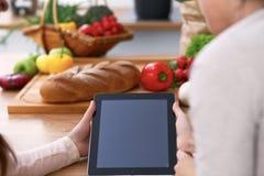 使用触感衰减器的两女性的人的手在厨房 两名妇女特写镜头做网上购物  图库摄影