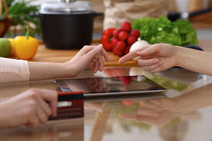 使用触感衰减器的两女性的人的手在厨房 两名妇女特写镜头做网上购物  库存照片