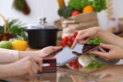 使用触感衰减器的两女性的人的手在厨房 两名妇女特写镜头做网上购物  免版税图库摄影