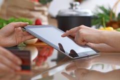 使用触感衰减器的两女性的人的手在厨房 两名妇女特写镜头做网上购物  免版税库存图片