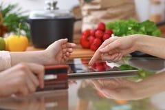 使用触感衰减器的两女性的人的手在厨房 两名妇女特写镜头做网上购物  库存图片