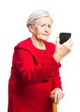 使用触摸屏机动性的生气年长妇女 免版税库存图片