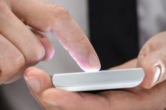 使用触摸屏电话的一个人的详细资料 免版税库存照片