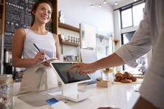 使用触摸屏的顾客付付款在咖啡店 免版税库存图片