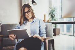 使用触摸板的年轻美丽的女学生在现代coworking的地方 工作在她的数字式片剂的自由职业者女孩 库存图片
