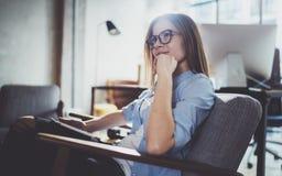 使用触摸板的年轻美丽的女学生在现代coworking的地方 工作在她的数字式片剂的自由职业者女孩 免版税库存图片